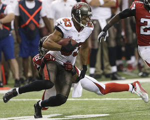Photo - Tampa Bay Buccaneers wide receiver Vincent Jackson (83) is tackled by Atlanta Falcons free safety Thomas DeCoud (28) during the first half of an NFL football game, Sunday, Oct. 20, 2013, in Atlanta. (AP Photo/John Bazemore)