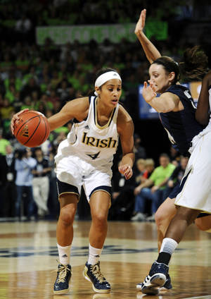 Photo - Notre Dame guard Skylar Diggins, left, drives the lane as Connecticut guard Kelly Faris defends during the first half of an NCAA college basketball game, Monday, March 4, 2013, in South Bend, Ind. (AP Photo/Joe Raymond)
