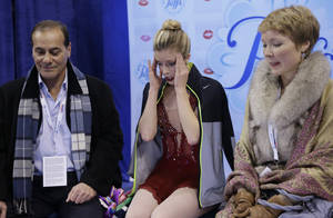 Photo - Ashley Wagner, middle, reacts after competing in the women's free skate as her coaches Rafael Arutunian, left, and Nadia Kanaeva, right, look on at the U.S. Figure Skating Championships Saturday, Jan. 11, 2014 in Boston. (AP Photo/Steven Senne)
