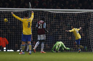 Photo - Arsenal's Theo Walcott, right, celebrates his second goal against West Ham United during their English Premier League soccer match at Upton Park, London, Thursday, Dec. 26, 2013. (AP Photo/Sang Tan)