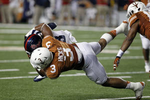 Photo - Texas linebacker Jordan Hicks (3) tackles Mississippi running back Jeff Scott (3) during the third quarter of an NCAA college football game Saturday, Sept. 14, 2013, in Austin, Texas. Ole Miss won 44-23. (AP Photo/Michael Thomas)