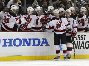 Photo - New Jersey Devils' Ilya Kovalchuk, center, is greeted by teammates on the bench after scoring in the second period of the NHL hockey game against the Pittsburgh Penguins Sunday, Feb. 10, 2013, in Pittsburgh. (AP Photo/Keith Srakocic)