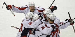 Photo -   Washington Capitals' Jason Chimera, top, joins teammates to celebrate a goal by Matt Hendricks against the Boston Bruins during the first period of Game 7 of an NHL hockey Stanley Cup first-round playoff series, in Boston on Wednesday, April 25, 2012. AP Photo/Charles Krupa)