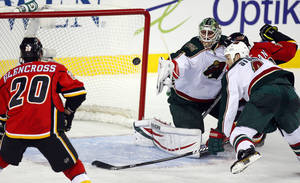 photo - Minnesota Wild goalie Niklas Backstrom, center, of Finland, and Clayton Stoner, right, watch the puck as they defend against Calgary Flames' Curtis Glencross during the second period of their NHL hockey game, Monday, Feb. 11, 2013, in Calgary, Alberta. (AP Photo/The Canadian Press, Jeff McIntosh)