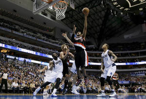Photo - Portland Trail Blazers power forward LaMarcus Aldridge, center, goes up for a shot as Dallas Mavericks' DeJuan Blair (45) and Monta Ellis (11) defend during the first half of an NBA basketball game, Saturday, Jan. 18, 2014, in Dallas. (AP Photo/Tony Gutierrez)