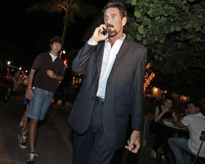 photo - Anti-virus software founder John McAfee talks on his mobile phone as he walks on Ocean Drive in the South Beach area of Miami Beach, Fla., on his way to dinner Wednesday, Dec 12, 2012. McAfee arrived in the U.S. on Wednesday night after being deported from Guatemala, where he had sought refuge to evade police questioning in the killing of a man in neighboring Belize.(AP Photo/Alan Diaz)