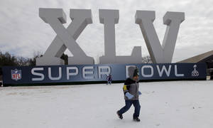 Photo - Javon Banks, 3, of San Antonio, plays on the ice and snow in front of a Super Bowl XLV logo outside the NFL Experience Wednesday, Feb. 2, 2011, in Dallas. Snow and ice blanked the area Tuesday and temperatures are forecast to remain below freezing for several days. The Pittsburgh Steelers will play the Green Bay Packers in Super Bowl XLV at Cowboys Stadium Sunday, Feb. 6, 2011. (AP Photo/David J. Phillip)