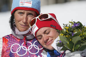 Photo - Norway's gold medal winner Marit Bjoergen, left, hugs bronze medal winner Heidi Weng during the flower ceremony of the women's cross-country 15k skiathlon at the 2014 Winter Olympics, Saturday, Feb. 8, 2014, in Krasnaya Polyana, Russia. (AP Photo/Dmitry Lovetsky)