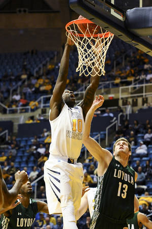 Photo - West Virginia's Eron Harris (10) tips in a basket during the first half of an NCAA college basketball game against Loyola Maryland, Monday, Dec. 2, 2013, in Morgantown, W.Va. (AP Photo/Andrew Ferguson)