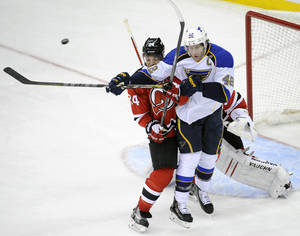 Photo - St. Louis Blues' David Backes (42) attempts to deflect the puck as he is checked by New Jersey Devils' Bryce Salvadore during the second period of an NHL hockey game Tuesday, Jan. 21, 2014, in Newark, N.J. (AP Photo/Bill Kostroun)