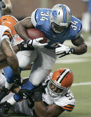photo -   In this Aug. 10, 2012 photo, Detroit Lions running back Keiland Williams (34) scores a touchdown after a 5-yard run as he is tackled by Cleveland Browns defensive tackle John Hughes (93) in the first quarter of an NFL preseason football game in Detroit. The Lions need options in their depleted backfield without Jahvid Best and Mikel Leshoure, and Keiland Williams gives them one as the first preseason game confirmed.(AP Photo/Duane Burleson)