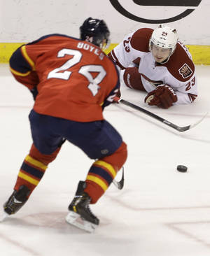 Photo - Florida Panthers right wing Brad Boyes (24) and Phoenix Coyotes defenseman Oliver Ekman-Larsson (23), of Sweden, battle for the puck during the second period of an NHL hockey game, Tuesday, March 11, 2014, in Sunrise, Fla. (AP Photo/Wilfredo Lee)