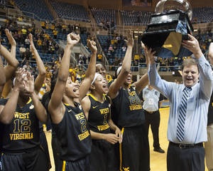 Photo - West Virginia's Mike Carey, right, celebrates a share of the Big 12 Conference championship after defeating Kansas during an NCAA college basketball game Tuesday, March 4, 2014, in Morgantown, W.Va. West Virginia won 67-60. (AP Photo/Andrew Ferguson)