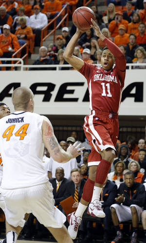 photo - Oklahoma's Isaiah Cousins (11) pass the ball as Oklahoma State's Philip Jurick (44) defends during the Bedlam men's college basketball game between the Oklahoma State University Cowboys and the University of Oklahoma Sooners at Gallagher-Iba Arena in Stillwater, Okla., Saturday, Feb. 16, 2013. Photo by Sarah Phipps, The Oklahoman
