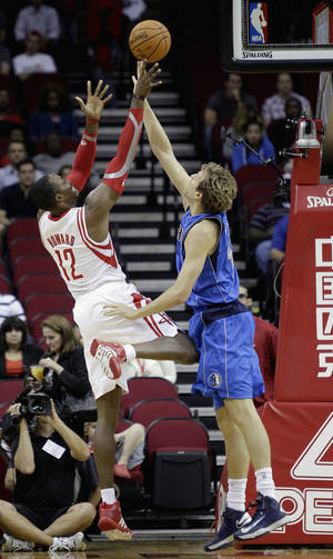 Photo - Houston Rocket's Dwight Howard, left, shoots a fade away over Dallas Maverick's Dirk Nowitzki, right, in the first half of a preseason NBA basketball game Monday, Oct. 21, 2013, in Houston. Houston won 100-95. (AP Photo/Bob Levey)