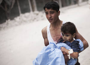 Photo -   RETRANSMISSION FOR ALTERNATIVE CROP - A Syrian youth holds a child wounded by Syrian Army shelling near Dar El Shifa hospital in Aleppo, Syria, Thursday, Oct. 11, 2012. (AP Photo/ Manu Brabo)