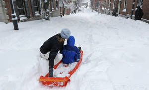 photo - A woman prepares to launch her child down a snow-covered street in the Beacon Hill neighborhood of Boston, Saturday, Feb. 9, 2013. The Boston area received about two feet of snow from a winter storm. A howling storm across the Northeast left the New York-to-Boston corridor shrouded in 1 to 3 feet of snow Saturday, stranding motorists on highways overnight and piling up drifts so high that some homeowners couldn't get their doors open. More than 650,000 homes and businesses were left without electricity. (AP Photo/Charles Krupa)