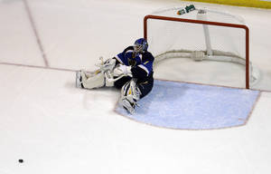 Photo - St. Louis Blues goalie Brian Elliott sits on the ice after giving up a goal to Los Angeles Kings' Jeff Carter during the second period of an NHL hockey game, Monday, Feb. 11, 2013, in St. Louis. The goal was Carter's second of the game against Elliott. (AP Photo/Jeff Roberson)