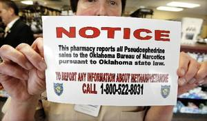 photo - Dani Lynch, Thrifty Pharmacy owner, holds up a  pseudoephedrine reporting sticker at Thrifty Pharmacy in Oklahoma City Tuesday, March 9, 2009. BY PAUL B. SOUTHERLAND