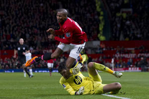 Photo - Manchester United's Ashley Young, right, appears to be brought down by Tottenham's goalkeeper Hugo Lloris during their English Premier League soccer match at Old Trafford Stadium, Manchester, England, Wednesday Jan. 1, 2014. (AP Photo/Jon Super)