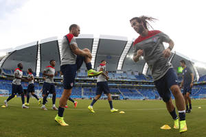Photo - In this photograph taken with a fisheye lens, United States players warm up during an official training session the day before the group G World Cup soccer match between Ghana and the United States at the Arena das Dunas in Natal, Brazil, Sunday, June 15, 2014.  (AP Photo/Julio Cortez)