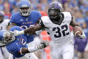 Photo -   TCU running back Waymon James (32) pushes Kansas cornerback Greg Brown (5) away as he runs for a gain during the first half of an NCAA college football game, Saturday, Sept. 15, 2012, in Lawrence, Kan. (AP Photo/Charlie Riedel)