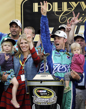 Photo -   Matt Kenseth celebrates in Victory Lane with his wife Katie and daughters Kaylin, left, and Grace, right, following his win in the NASCAR Sprint Cup Series auto race at Kansas Speedway in Kansas City, Kan., Sunday, Oct. 21, 2012. (AP Photo/Colin E. Braley)