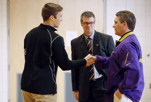 Photo - Minnesota State, Mankato defensive back Sam Thompson left, shakes hands with coach Todd Hoffner, as athletic director Kevin Buisman watches on Thursday April 17, 2014, in Mankato , Minn. Players ended their boycott of spring practice and said Thursday they will play for Hoffner, who was reinstated after being exonerated of having child pornography on his cellphone. (AP Photo/Star Tribune, Jerry Holt) ST. PAUL OUT  MINNEAPOLIS-AREA TV OUT  MAGS OUT