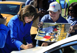 Photo -   U.S. Secretary of Labor Hilda Solis signs autographs outside the Flat Rock Assembly in Flat Rock, Mich., Monday, Sept. 10, 2012. The plant, formerly known as AutoAlliance International will continue to produce the Mustang and add the Fusion next year. Flat Rock Assembly will be the U.S. producer of the Fusion, employing 2,900 workers on both vehicle lines. (AP Photo/Carlos Osorio)