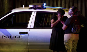 Photo -   A woman cries at the scene of a police shooting on Thursday April 5, 2012 in Austin, Texas. An Austin police officer fatally shot a man after a traffic stop that authorities said quickly escalated. (AP Photo/Austin American-Statesman, Jay Janner) MAGS OUT; NO SALES; INTERNET AND TV MUST CREDIT PHOTOGRAPHER AND STATESMAN.COM
