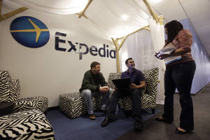 photo - In this Tuesday, Jan. 15, 2013, photo, Expedia analytics team workers Mike Brown, left, Saurin Pandya and Prashanti Tata chat in an alcove set up for employees  in Bellevue, Wash. Soaring hotel bookings pushed revenue higher at Expedia Inc., but the online travel agency's fourth-quarter profit fell 90 percent because of money it set aside to appeal a tax dispute in Hawaii. (AP Photo/Elaine Thompson)