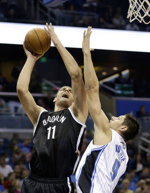 Photo - Brooklyn Nets' Brook Lopez (11) attempts a shot over Orlando Magic's Nikola Vucevic, of Montenegro, during the first half of an NBA basketball game in Orlando, Fla., Sunday, Nov. 3, 2013. (AP Photo/John Raoux)