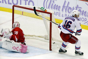 Photo - New York Rangers center Derick Brassard (16) scores the winning goal on Detroit Red Wings goalie Jimmy Howard during the first overtime period of an NHL hockey game Saturday, Oct. 26, 2013, in Detroit. The Rangers won 3-2. (AP Photo/Duane Burleson)