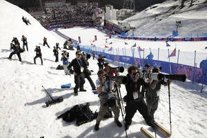 Photo - Photographers take pictures during the men's and women's snowboard parallel slalom quarterfinals at the Rosa Khutor Extreme Park, at the 2014 Winter Olympics, Saturday, Feb. 22, 2014, in Krasnaya Polyana, Russia. (AP Photo/Jae C. Hong)