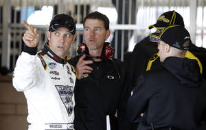 Photo - Driver Matt Kenseth, left, talks with his crew in his garage after practice for the NASCAR Sprint Cup series auto race in Fontana, Calif., Saturday, March 22, 2014.(AP Photo/Alex Gallardo)