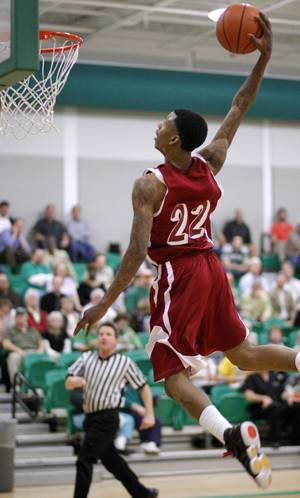 Photo - Ardmore's Nino Jackson dunks the ball against Bishop McGuinness during a high school basketball game at Bishop McGuinness in Oklahoma City, Tuesday, Feb. 15, 2011.  Photo by Bryan Terry, The Oklahoman ORG XMIT: KOD