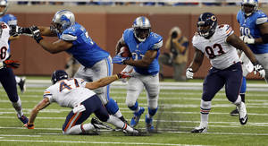Photo - Detroit Lions running back Reggie Bush (21) breaks through the Chicago Bears defense during the first quarter of an NFL football game at Ford Field in Detroit, Sunday, Sept. 29, 2013. Bush rushed for 139 yards in the Lions' 40-32 win. (AP Photo/Paul Sancya)