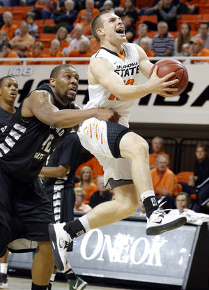 Photo - Oklahoma State's Phil Forte (10) is folded by Portland State's Lamont Prosser (42) during the college basketball game between Oklahoma State University and Portland State, Sunday,Nov. 25, 2012. Photo by Sarah Phipps, The Oklahoman