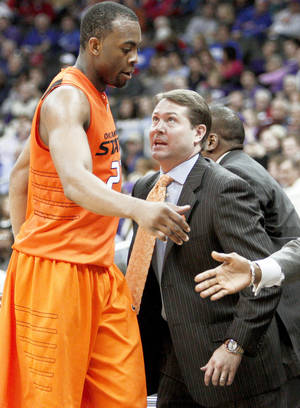 Photo - OSU's James Anderson talks with coach Travis Ford as he exits Thursday's 83-64 loss to Kansas State in the Big 12 Tournament. PHOTO BY BRYAN TERRY, THE OKLAHOMAN