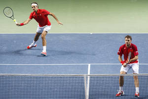 Photo - Switzerland's Roger Federer, left, next to his doubles partner Stanislas Wawrinka, right, returns the ball to Kazakhstan's Aleksandr Nedovyesov, and Andrey Golubev, during their doubles match of the tennis Davis Cup World Group quarterfinal match between Switzerland and Kazakhstan,  in Geneva, Switzerland, Saturday, April 5, 2014.(AP Phtoo/Keystone,Salvatore Di Nolfi)