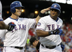 Photo -   Texas Rangers' Josh Hamilton, left, congratulates Adrian Beltre, right, on his two-run home run off of Cleveland Indians' Jeanmar Gomez that scored Hamilton in the first inning of a baseball game, Wednesday, Sept. 12, 2012, in Arlington, Texas. (AP Photo/Tony Gutierrez)
