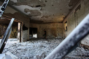 "Photo - FILE - This Sept. 13, 2012 file photo shows a man walking in the rubble of the damaged U.S. consulate, after an attack that killed four Americans, including Ambassador Chris Stevens on the night of Tuesday, Sept. 11, 2012, in Benghazi, Libya. To congressional Republicans, ""Benghazi"" is shorthand for incompetence and cover-up. Democrats hear it is as the hollow sound of pointless investigations.  (AP photo/Mohammad Hannon, File)"