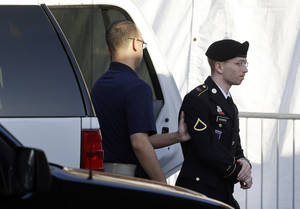 Photo - Army Pfc. Bradley Manning, right, is escorted from a security vehicle to a courthouse in Fort Meade, Md., Wednesday, April 10, 2013, before a pretrial military hearing. Manning, who is charged with causing hundreds of thousands of classified documents to be published on the secret-sharing website WikiLeaks, is scheduled to face a court martial in June. (AP Photo/Patrick Semansky)