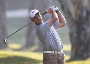 Photo - David Higgins of Ireland hits a ball on the 9th hole during the Hong Kong Open golf tournament in Hong Kong Thursday, Dec. 5, 2013.   (AP Photo/Kin Cheung)