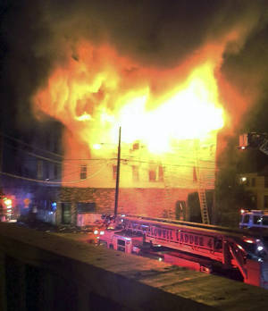 Photo - In this photo provided by Kevin Moav, fire engulfs the top floors of a three-story apartment and business building Thursday, July 10, 2014, in Lowell, Mass. Officials confirmed that seven people died in the fast-moving pre-dawn fire. (AP Photo/Kevin Moav)