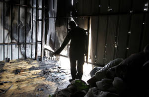 Photo -   A Palestinian stands in a factory hit by an Israeli tank shell in Beit Hanoun, northern Gaza Strip, Sunday, Nov. 11, 2012. Hostilities along the Gaza-Israel border escalated sharply over the weekend, with bombardments from Gaza causing rare Israeli casualties and Israeli strikes killing at least six Palestinians. (AP Photo/Hatem Moussa)