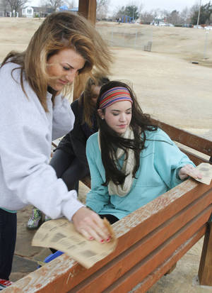 Photo - Courtney McCausland, left, and Emily Blasingame sand old paint off of park benches during the UCO Big Event Day at Douglas Park in Oklahoma City.  Photos By Paul Hellstern, The Oklahoman