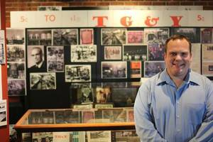 Photo - Chisholm Trail Museum director Adam Lynn stands in front of part of the museum's TG&Y exhibit that chronicles the early history of the chain and includes numerous store branded items. The exhibit runs through July. <strong>MATT PATTERSON - MATT PATTERSON</strong>