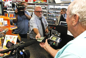 Photo - In this Nov. 29, 2012 file photo, television cameras rolling, as store manager Bob Chebat, middle, hands over Wes Prinzen's, right,  modest $4 winnings, at a 4 Sons Food Store where one of the winning tickets in the $579.9 million Powerball jackpot was purchased in Fountain Hills, Ariz.  When two winning tickets for a record Powerball jackpot were claimed last month, the world focused on the winners. One, from Missouri, showed up at the newsconference, while the other, in Arizona, chose to remain anonymous. Releasing information on the lottery winners reflects a broader debate playing out in state Legislatures and lottery offices nationwide: Should the winners' names be made public?(AP Photo/Ross D. Franklin, file)