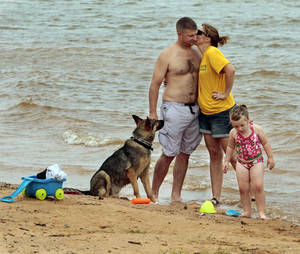 Photo - Sam and Melissa Helmick, of Midwest City, share a kiss while daughter Elexus and dog Fara play on the beach at Lake Thunderbird State Park.